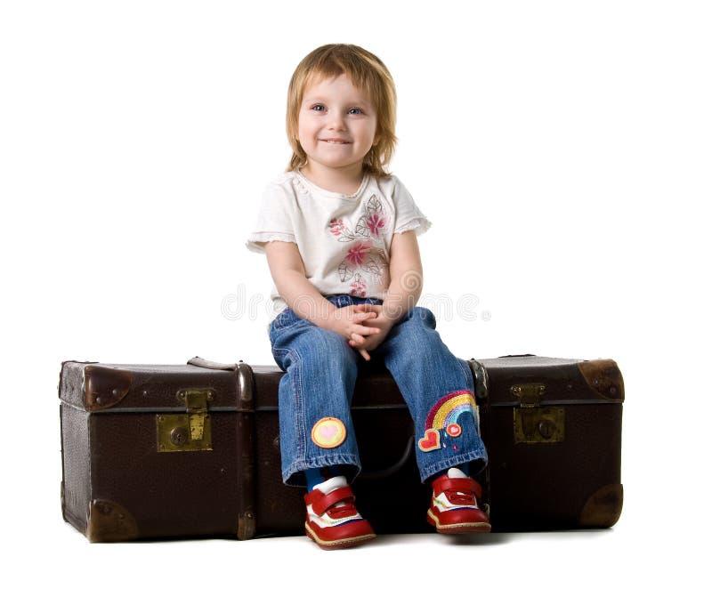 Bebê que senta-se em uma mala de viagem velha fotos de stock royalty free