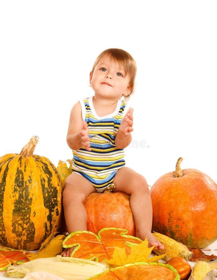 Bebê que senta-se na abóbora imagem de stock