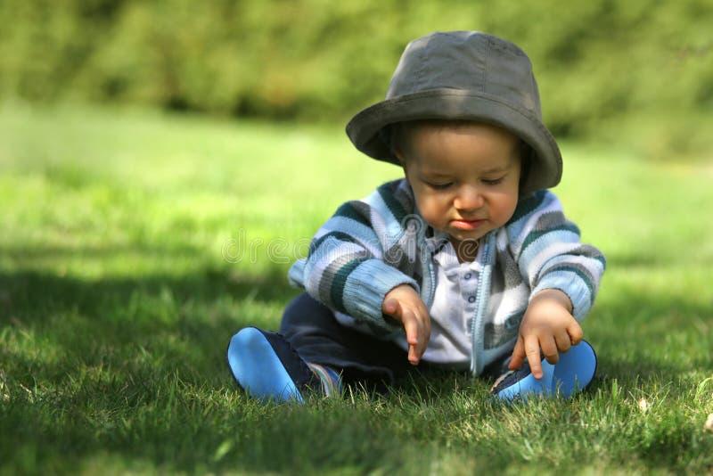 Bebê que senta-se na grama fotografia de stock royalty free