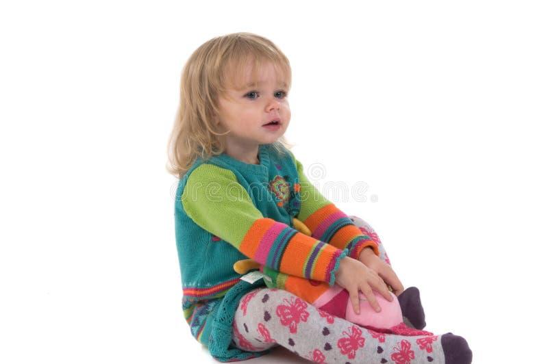 Bebê que senta-se no assoalho fotografia de stock