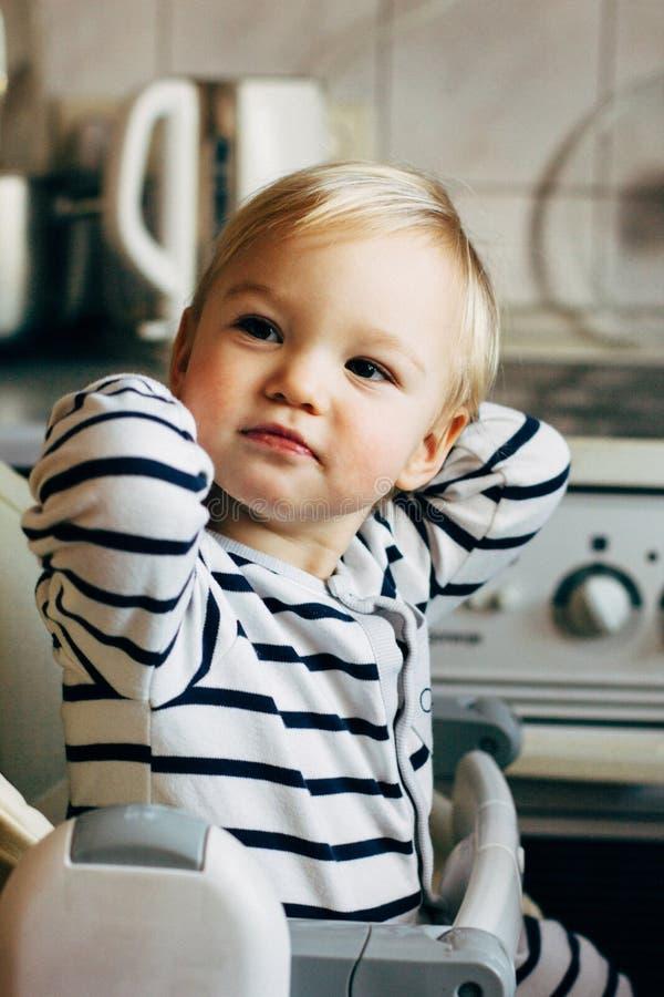 Bebê que senta-se no highchair A criança senta-se na tabela vazia e na espera para sua alimentação É criança bonito loura no desg fotografia de stock
