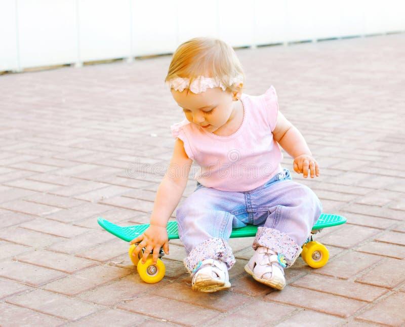 bebê que senta-se no skate imagem de stock