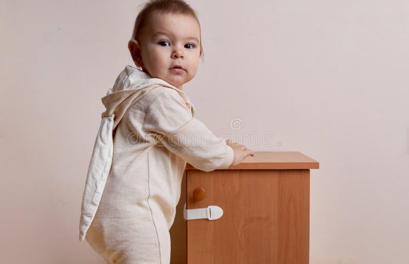 Bebê que tenta abrir o armário com casa segura de impermeabilização do fechamento do bebê fotos de stock royalty free