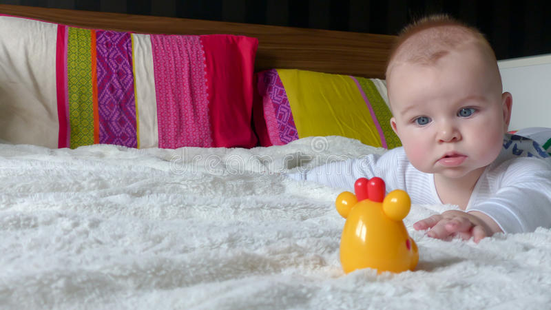 Bebê que tenta alcançar o brinquedo imagens de stock