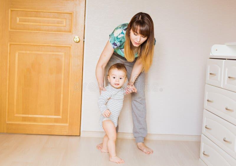 Bebê que toma primeiras etapas com ajuda da mãe imagens de stock