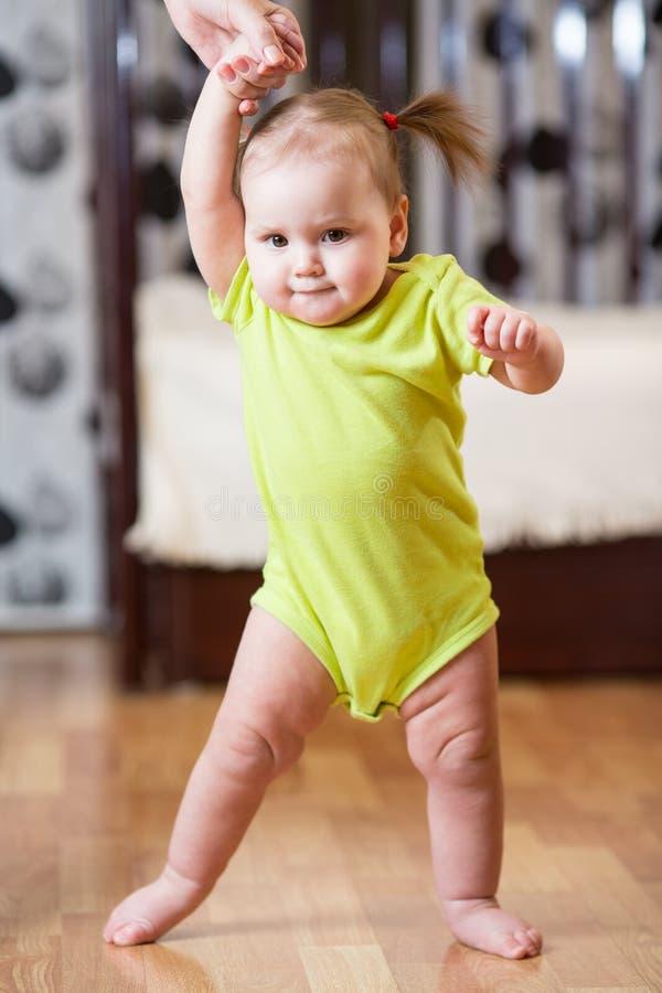 Bebê que toma primeiras etapas com ajuda do ` s da mãe em casa fotografia de stock