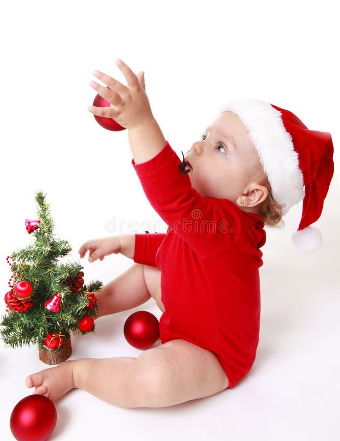 Bebê que veste um chapéu de Santa Claus, jogando com bolas vermelhas, perto da árvore de Natal imagem de stock