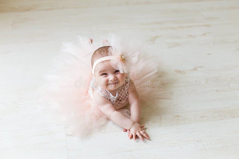 Bebê que veste um tutu do pêssego Bebê de sorriso bonito que encontra-se no assoalho no fundo cremoso Sorriso adorável imagem de stock