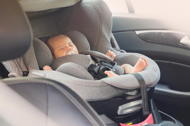 Bebê recém-nascido bonito asiático que dorme no banco de carro moderno imagens de stock