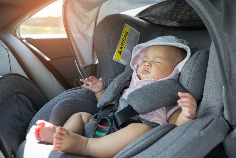 Bebê recém-nascido bonito asiático que dorme no banco de carro moderno fotos de stock