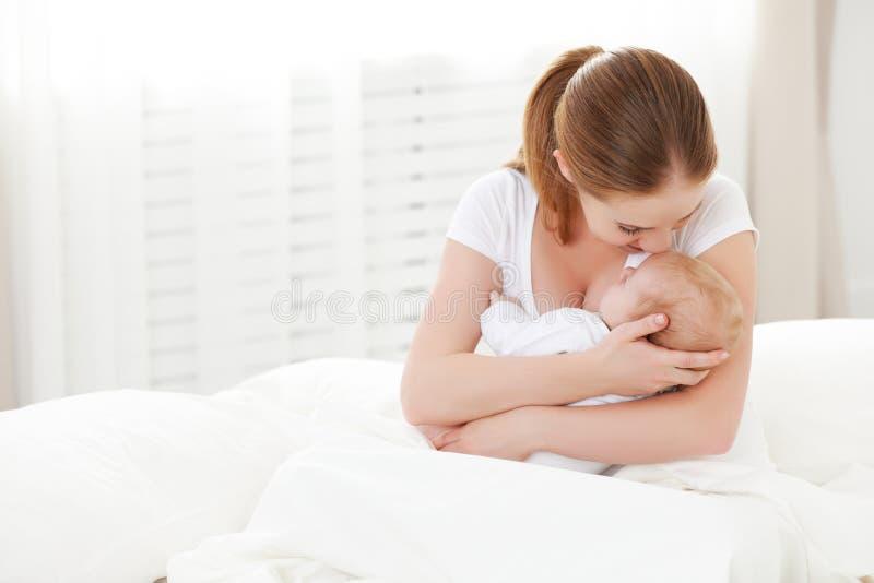 Bebê recém-nascido da família feliz na mãe do abraço no branco fotografia de stock royalty free