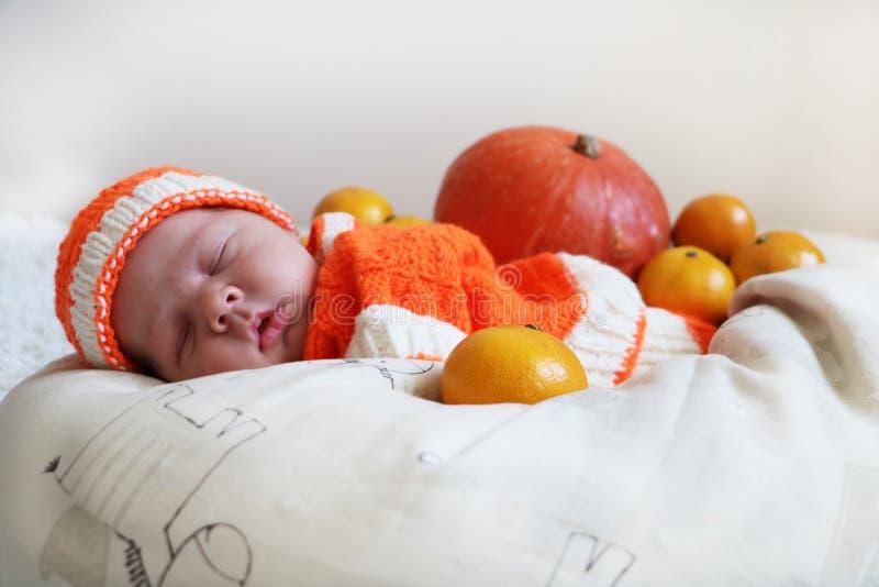 Bebê recém-nascido de sono bonito em uma abóbora feita malha ou em um costu alaranjado fotografia de stock