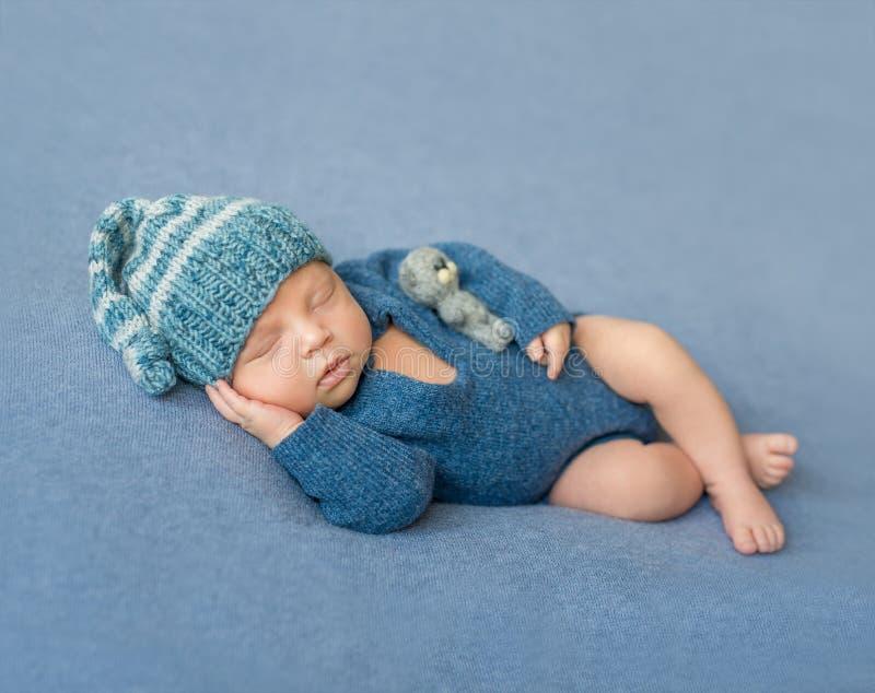 Bebê recém-nascido de sono no fato-macaco e no chapéu azuis foto de stock royalty free