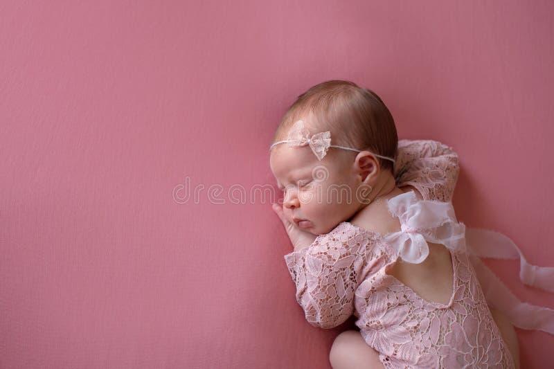 Bebê recém-nascido de sono que veste um Romper cor-de-rosa do laço foto de stock royalty free