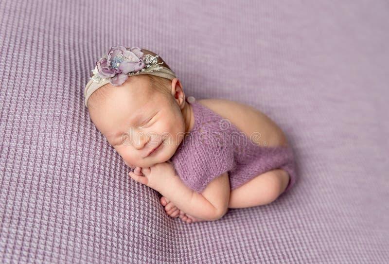 Bebê recém-nascido pequeno no bodysuit roxo que sorri ao dormir imagens de stock