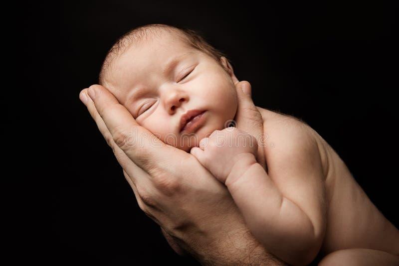 Bebê recém-nascido que dorme no pai Hand, retrato recém-nascido do estúdio da criança fotos de stock royalty free