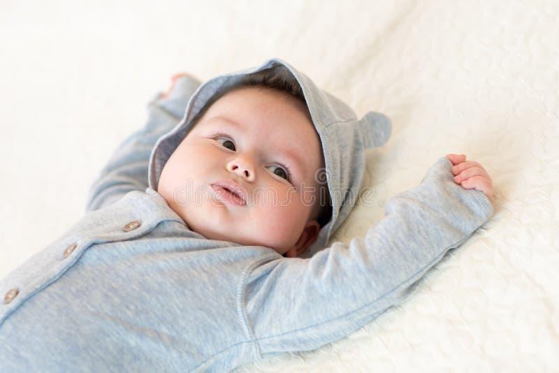 Bebê recém-nascido que encontra-se em sua parte traseira em uma colcha branca foto de stock royalty free