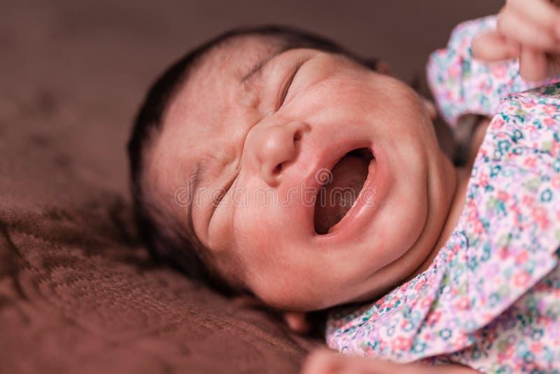 Bebê recém-nascido que encontra-se para baixo e que grita com grampos imagem de stock