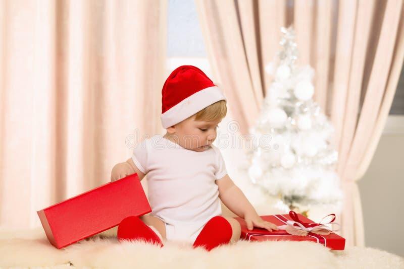 Bebê Santa que abre uma caixa de presente vermelha grande fotos de stock royalty free