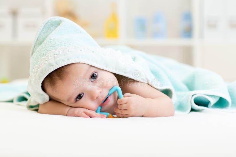 Bebê sob a toalha após o banho em casa imagens de stock