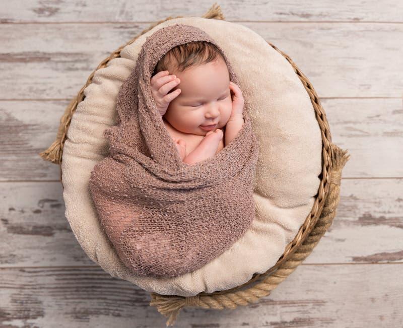 Bebê sonolento envolvido com pés e mãos dobrados na cabeça foto de stock