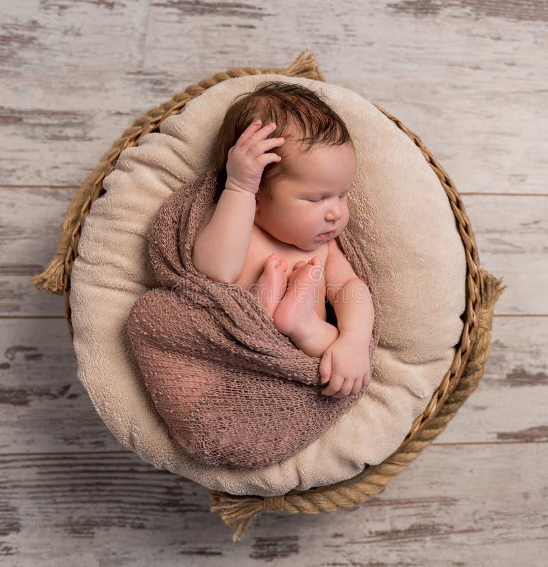 Bebê sonolento envolvido com pés e mãos dobrados na cabeça imagens de stock royalty free