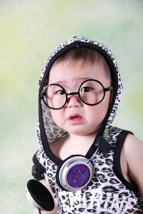 Bebê triste com os vidros e os fones de ouvido que sentam-se para baixo e que gritam fotografia de stock royalty free