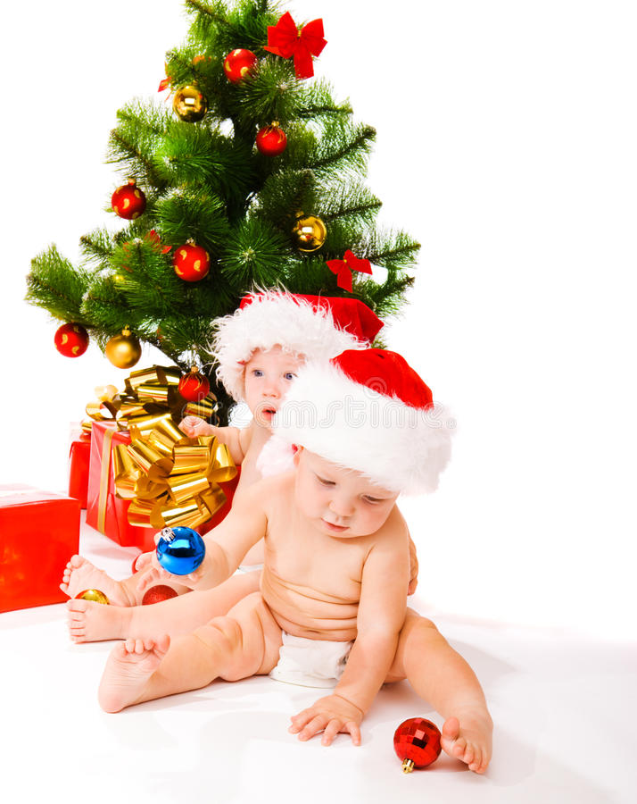 Bebês ao lado da árvore de Natal fotos de stock