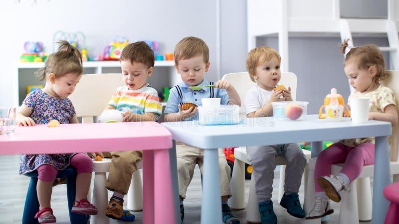 Bebês do berçário que comem o alimento As crianças têm o almoço na guarda foto de stock