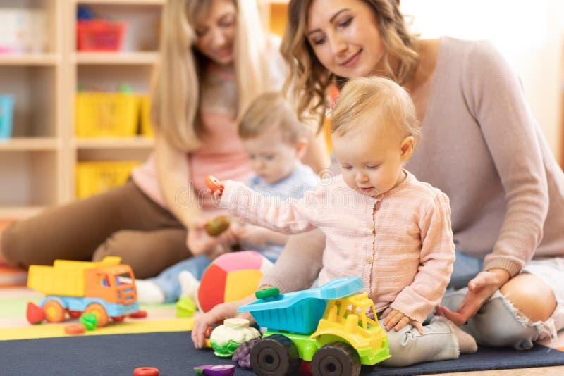 Bebês do berçário que jogam com os adultos no centro de centro de dia fotos de stock royalty free