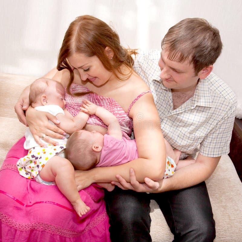 Bebês gêmeos amamentando em casa fotos de stock