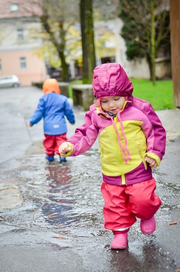 Bebês gêmeos na roupa da chuva imagens de stock