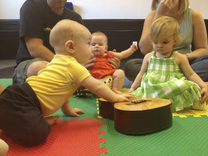 Bebês no rastejamento da classe de música à guitarra fotos de stock royalty free