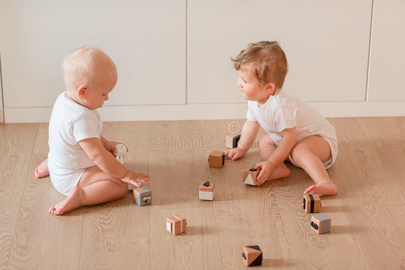 Bebês pequenos bonitos que jogam com blocos de madeira fotografia de stock
