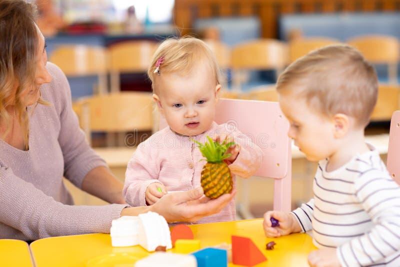 Bebês que aprendem os frutos que jogam brinquedos com o professor no berçário foto de stock
