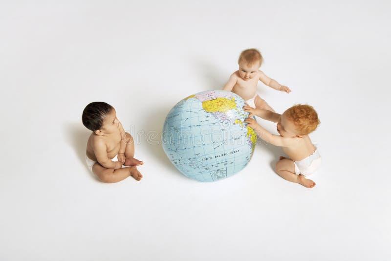 Bebês que jogam com globo imagem de stock