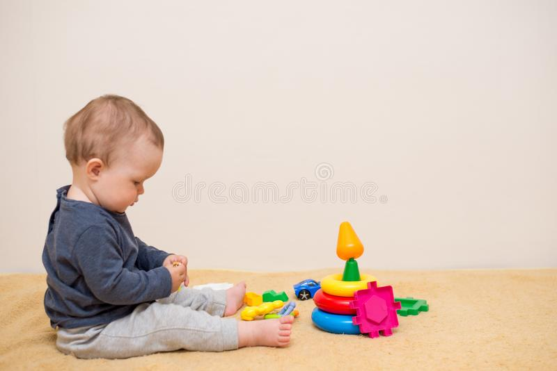 Beb? ador?vel que joga com brinquedos educacionais Fundo com espa?o da c?pia Crian?a saud?vel feliz que tem o divertimento em cas imagem de stock