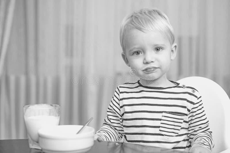 Beb? bonito do menino que come a crian?a do caf? da manh? para comer o papa de aveia Os olhos azuis bonitos do menino da crian?a  fotografia de stock royalty free