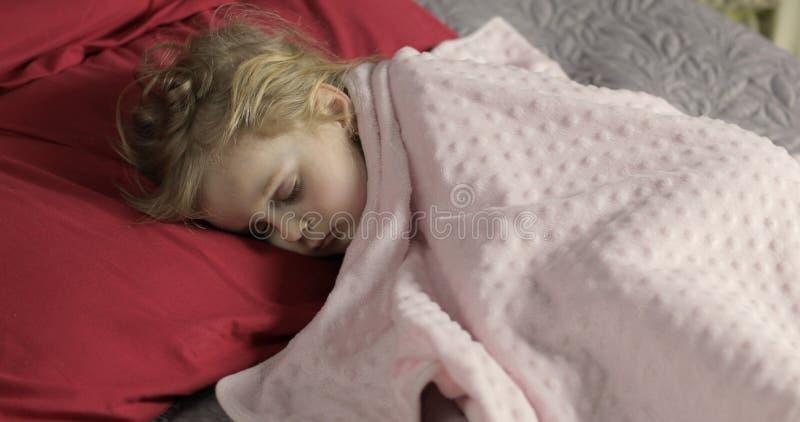 Beb? bonito que dorme na cama em casa Menina que dorme na luz da manh? imagem de stock royalty free