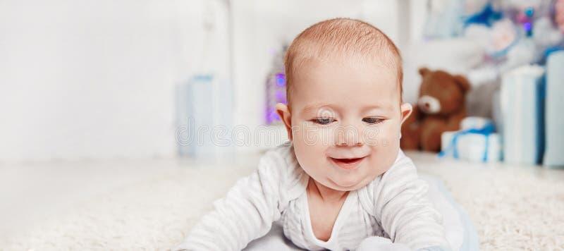 Beb? bonito que miente en la alfombra en la sala de estar acogedora imágenes de archivo libres de regalías