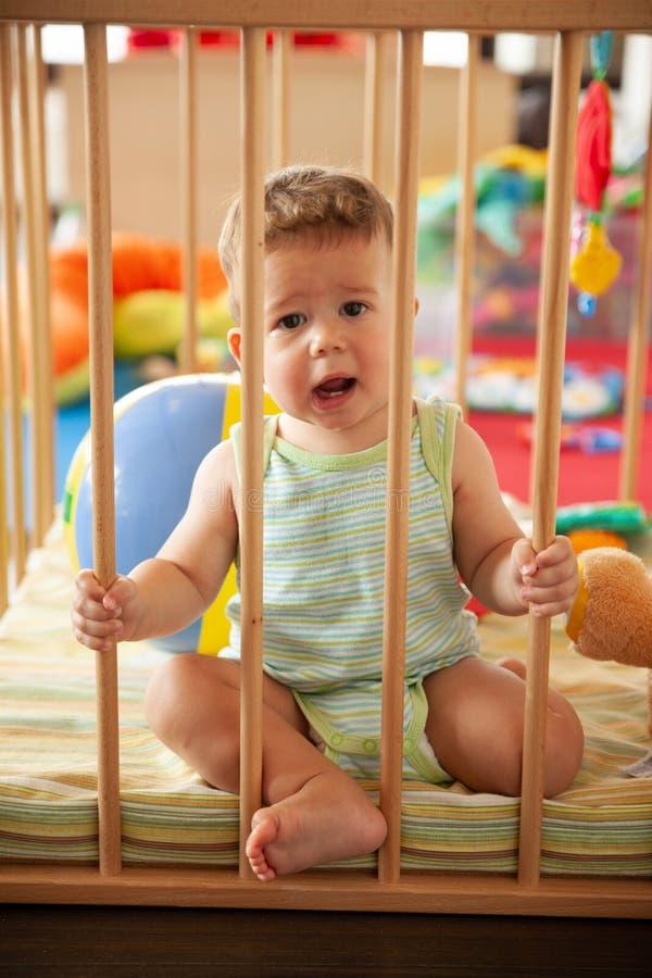 Beb? de sorriso bonito que olha atrav?s das barras de madeira de sua ucha ou imagens de stock royalty free