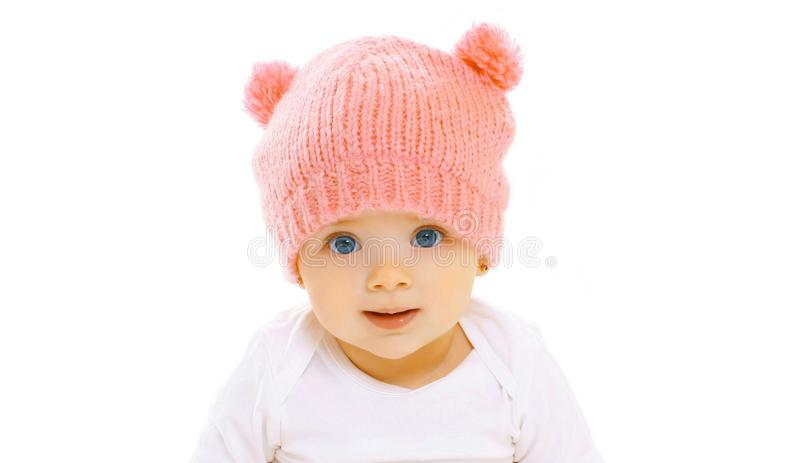 Beb? de sorriso feliz do close-up do retrato no chap?u cor-de-rosa feito malha no branco imagem de stock
