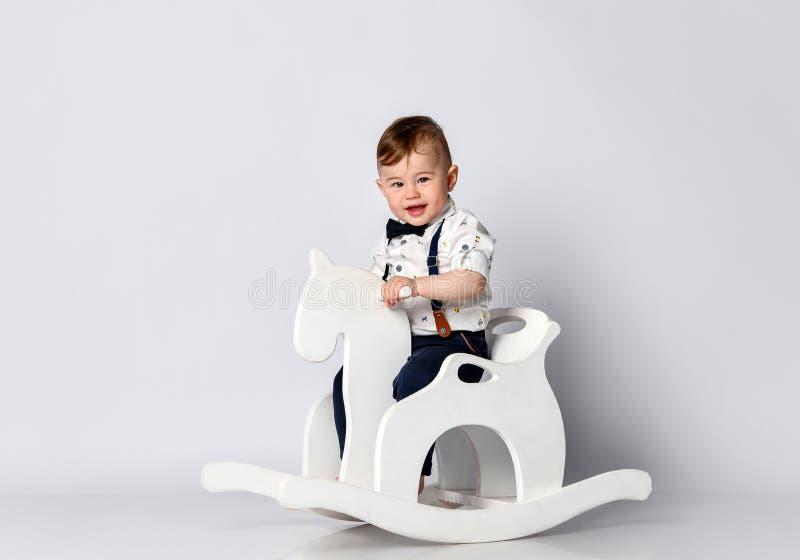 Beb? engra?ado que senta-se no cavalo do brinquedo foto de stock