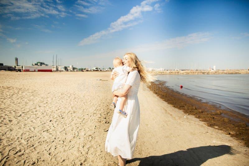Beb? feliz de los huges de la madre La madre celebra al ni?o en sus brazos, beb? que abraza a la mam? imagenes de archivo