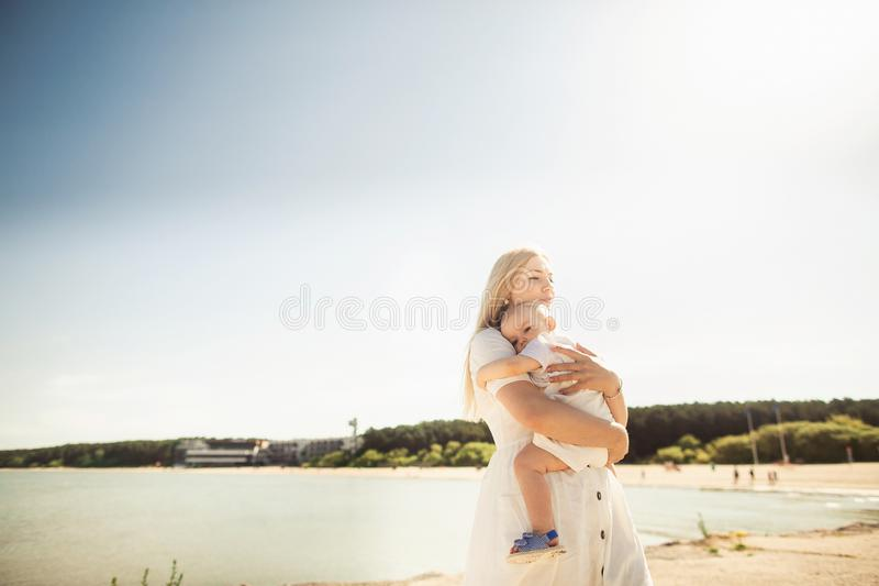 Beb? feliz de los huges de la madre La madre celebra al ni?o en sus brazos, beb? que abraza a la mam? fotos de archivo