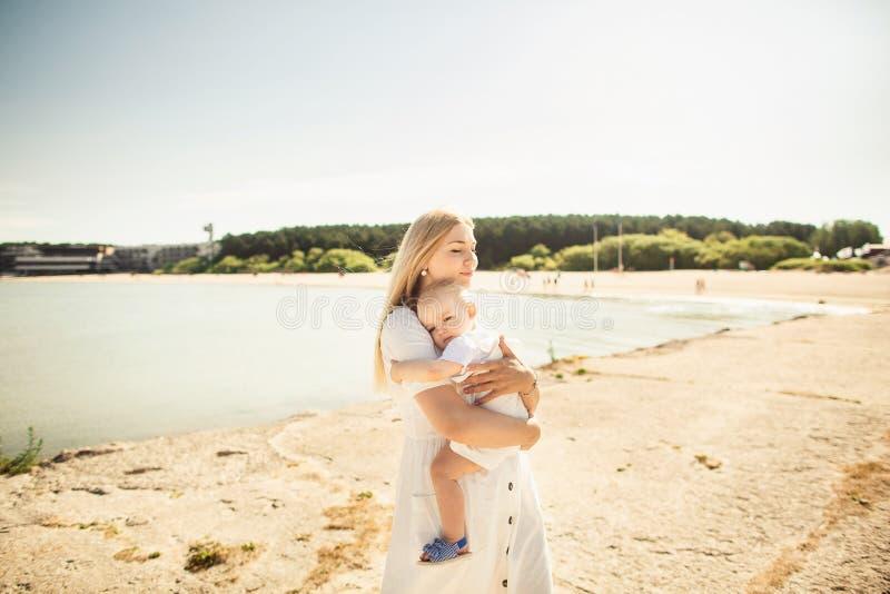 Beb? feliz de los huges de la madre La madre celebra al ni?o en sus brazos, beb? que abraza a la mam?, primer fotografía de archivo
