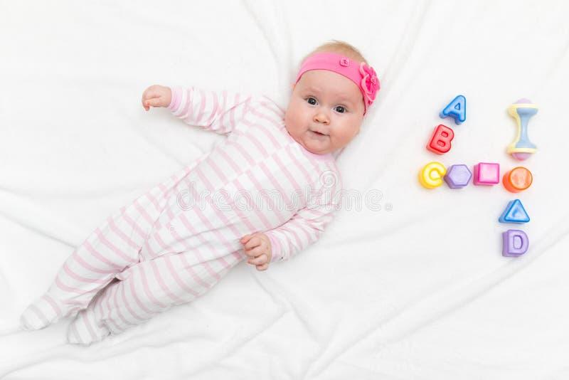 Beb? idoso bonito de quatro meses envolvido em toalhas ap?s o chuveiro na cama em casa fotos de stock