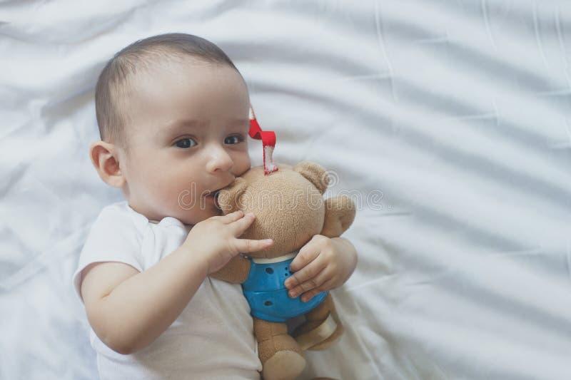 beb? 6-8-month-old que miente juguet?namente en cama Peque?o beb? encantador del mes 6-7 en el mono blanco Beb? en el lecho blanc imagen de archivo