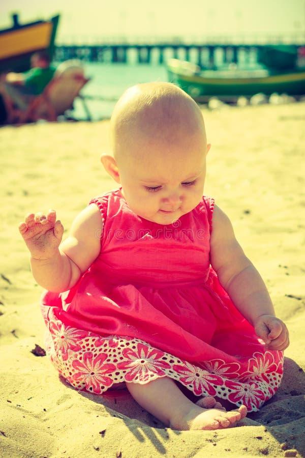 Beb? pequeno que senta-se e que joga na praia fotografia de stock royalty free