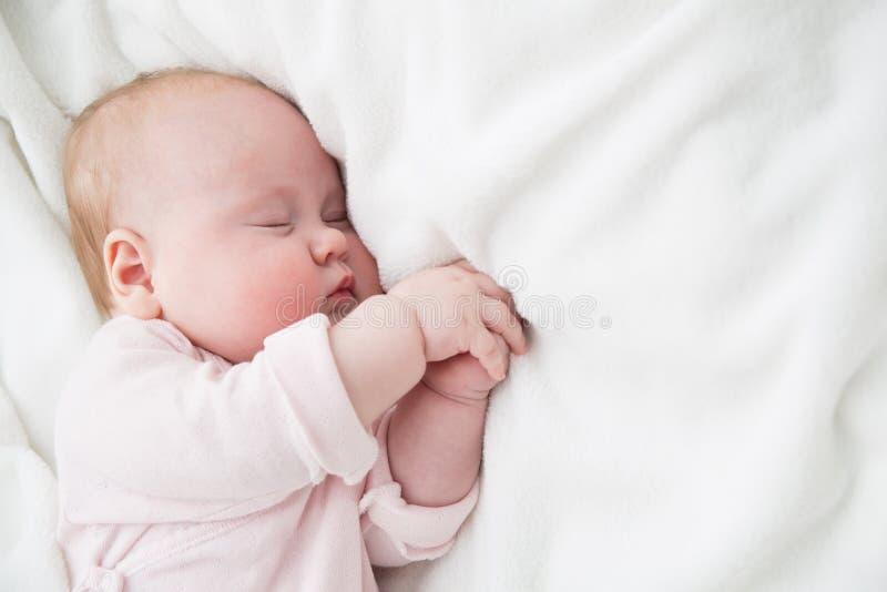 Beb? que dorme, 3 meses de crian?a idosa no sono cor-de-rosa de pano em uma cobertura branca, crian?a adormecida na cama fotos de stock royalty free